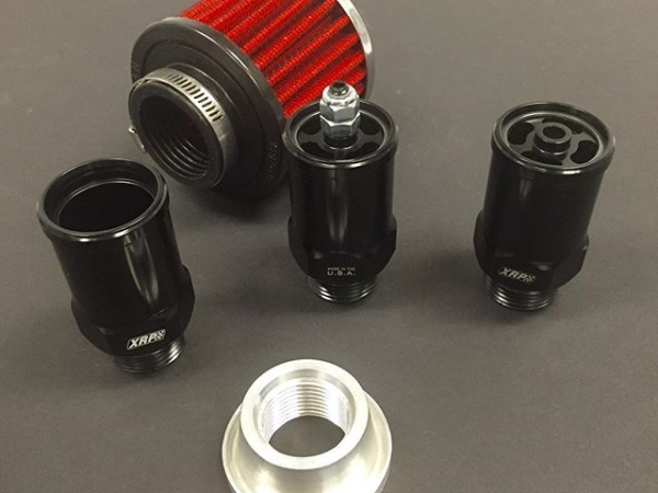 "New engine crankcase breather adapters from XRP shown in three styles. From left to right:  1) Straight through tube only.  2) One-way pop off with fully adjustable engine vacuum control. 3) One-way pop off with normally fully closed check valve, non adjustable.  Black anodized aluminum. All have a -12 male O-Ring boss thread and may use any commonly available 1-3/8"" crankcase filter. (Not included) Also shown is an aircraft style -12 female O-Ring boss weld-on port, 6061-T6 aluminum, with raised flange base that is designed to prevent thread and seal area distortion when welded. (Sold separately"